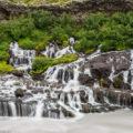 Die Wasserfälle des Hraunfossar entspringen dem Gestein